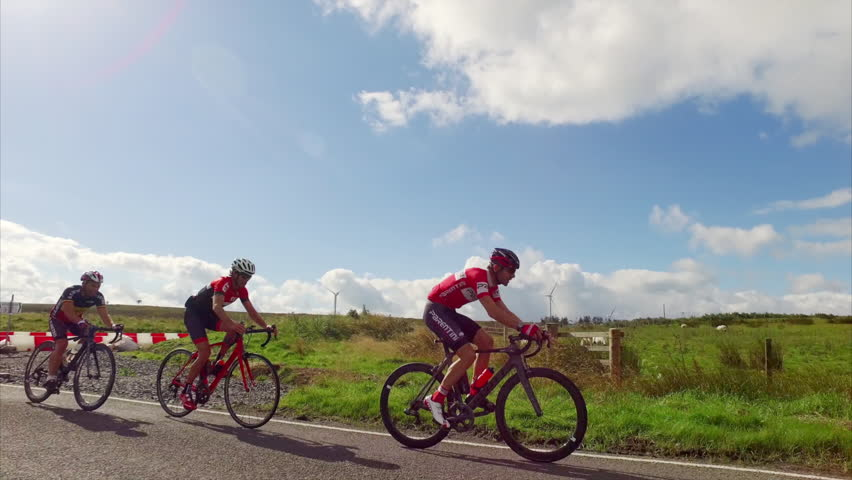 CATCLEUGH, ENGLAND, UK - AUGUST 26, 2016: A side view of a group of cycling athletes out on a training ride on the country roads in the UK countryside on a sunny day.  | Shutterstock HD Video #20272444