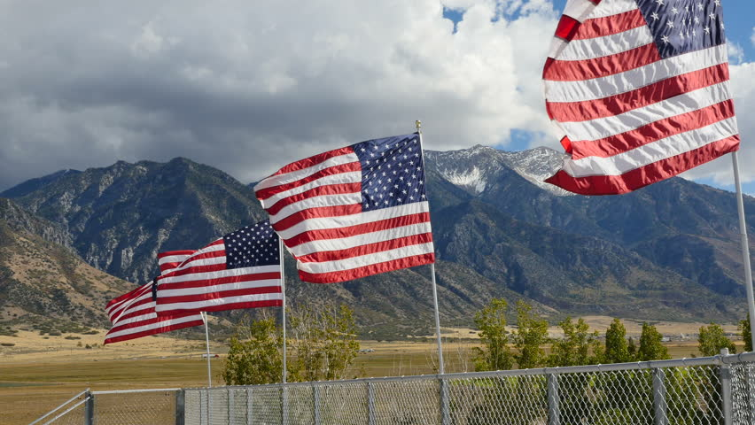 YOUNG LIVING FARMS, MONA, UTAH - SEPTEMBER 2016: Close up-Sunlit American flags wave gently in the wind against a dark cloudy sky and dark mountain backdrop. | Shutterstock HD Video #20378266