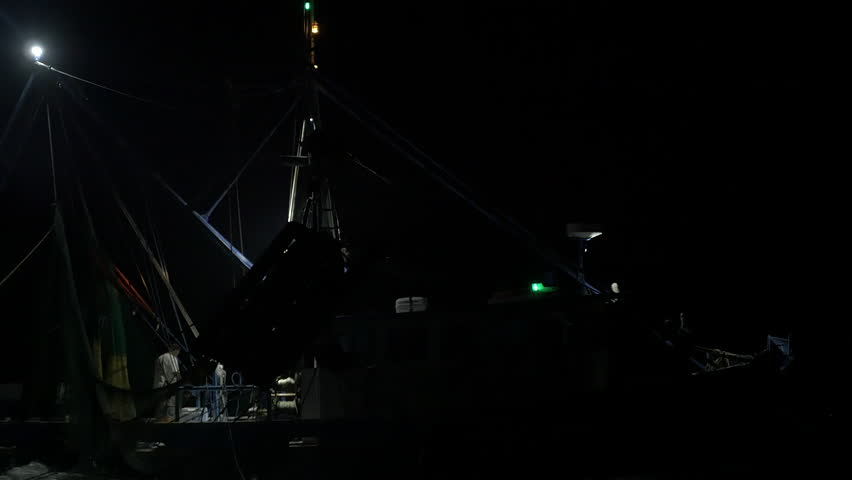 Shrimping trawler sails out to sea at night to fish with its nets down.