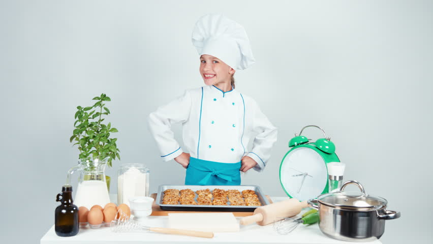 Happy chef cook girl child 7-8 years old has baking tray with biscuits and smiling at camera. Hand ok. Isolated on white | Shutterstock HD Video #20423923