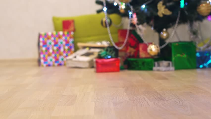 Little smiling baby boy feets run near garland on a background of Christmas tree and gift boxes with ribbon. | Shutterstock HD Video #20471011