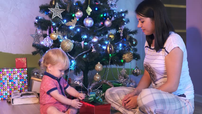 Christmas gift with light surprise. Mother and her Little baby boy opens a Christmas present and smile and laugh. Mom and her child waiting New Year 2017, happy family concept, slow motion | Shutterstock HD Video #20471029