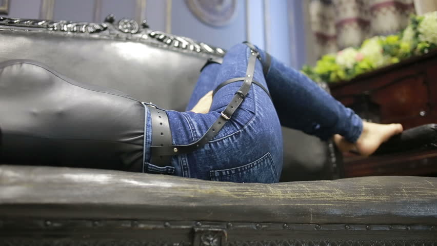 Girl in jeans with leather garter new fashion trends. straps on the hips | Shutterstock HD Video #20484745