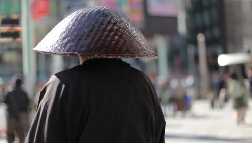 Unidentified monk from behind praying in a busy shopping district with blurred out pedestrians in Tokyo, Japan