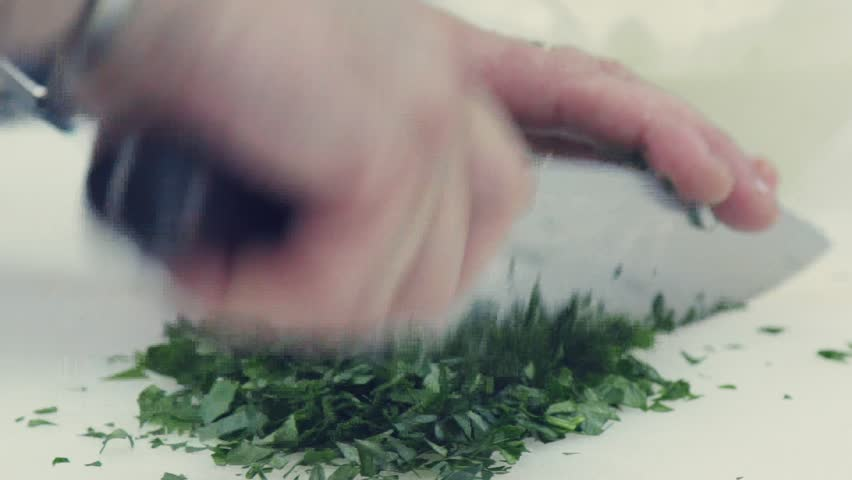 Close-up of cutting Dill and parsley. Cook cutting Dill and parsley with a sharp knife. Professional Cook Chopping Dill and parsley. Male chef hands are cutting raw Dill for further cooking #20728888