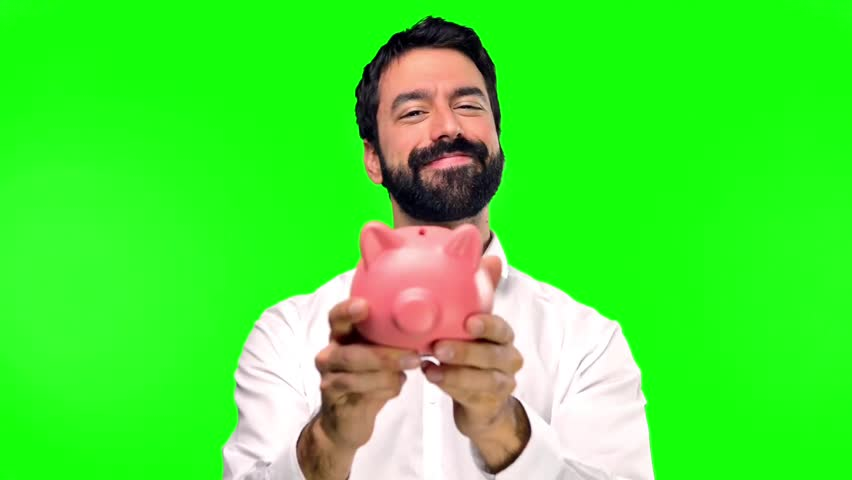Handsome man holding a piggybank on green screen chroma key | Shutterstock HD Video #20835331