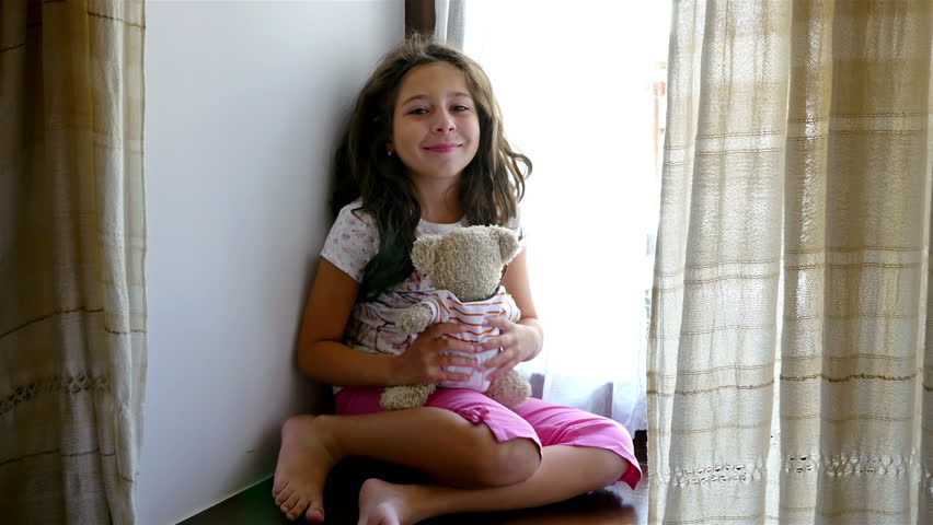 Cute little girl sitting on the windowsill, playing and hugging her bear toy | Shutterstock HD Video #20907412