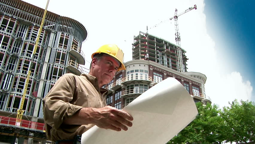 architect looking at building plans, then rolling them up and smiling at the camera. - HD stock video clip