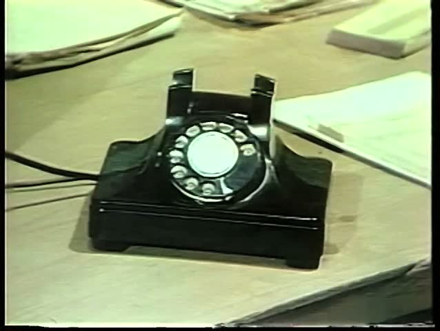 Man holding small notebook talking on rotary phone