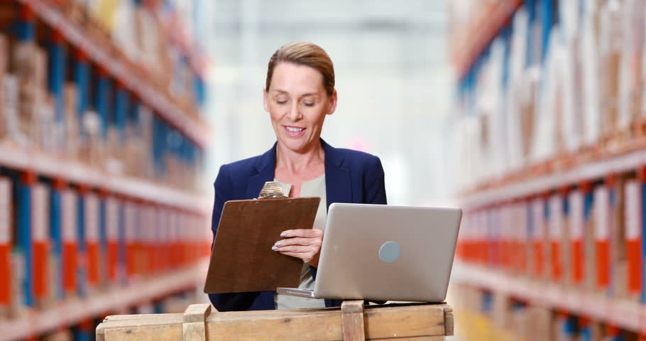 Female warehouse manager writing on clipboard and using laptop in warehouse 4k   Shutterstock HD Video #21124474