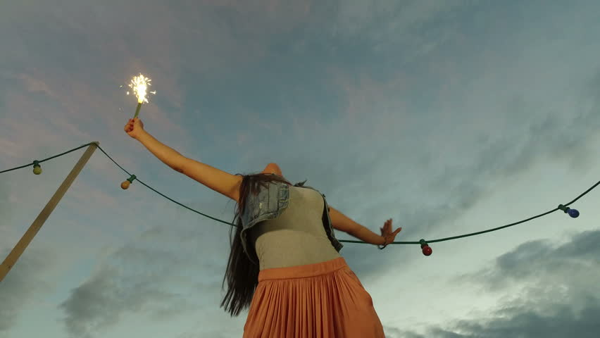 Front low angle shot of brunette woman jumping with firework candle on the rooftop terrace