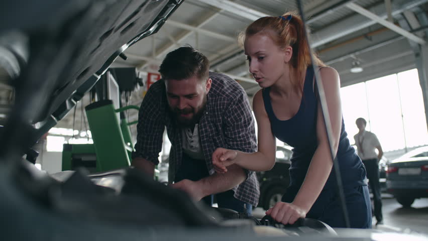 Man and woman in mechanic uniform checking details under car hood and fixing the breakdown | Shutterstock HD Video #21259942