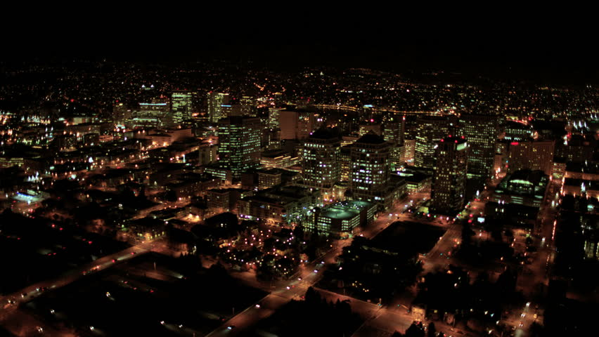 Aerial night illuminated cityscape view of rolling city streets modern buildings North America