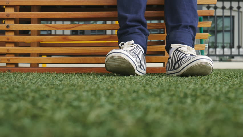 Female feet in jeans and sports shoes. Sneakers are on a wooden bench in a park close-up. Woman resting on the bench after the walk. #21380326