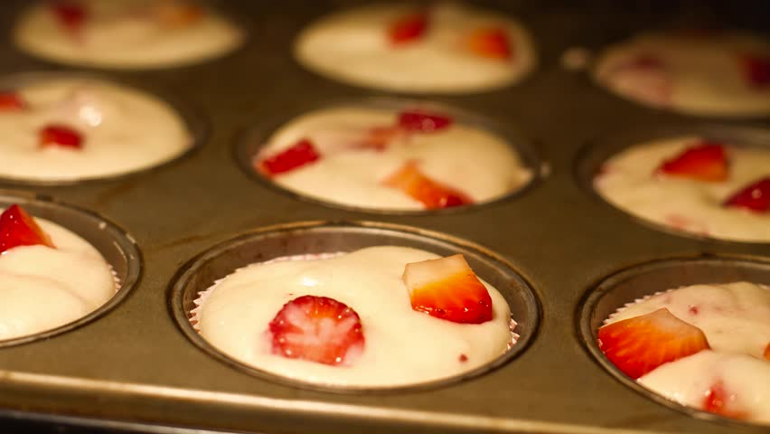 Homemade strawberry muffins in oven, shallow DOF, time lapse