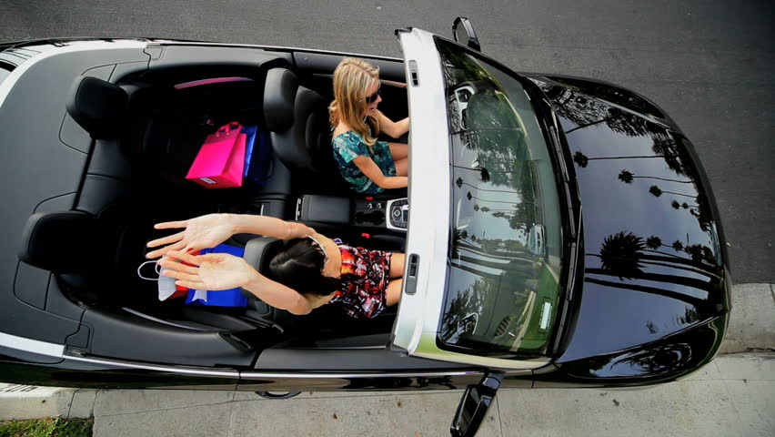 Girls with designer shopping bags from Rodeo Drive in luxury sports car