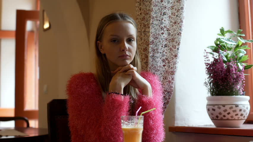 Pretty, stylish girl sitting in the cafe and doing serious look to the camera  | Shutterstock HD Video #21525235