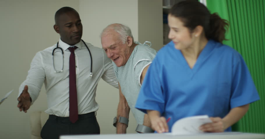 4K Caring medical workers in hospital assisting elderly man on crutches (UK-Oct 2016) | Shutterstock HD Video #21574501