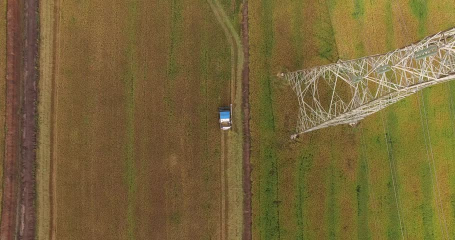 Aerial view flying over the top of a combine harvester and tractor and electricity tower as it empties the rice's in a field on a summers day. | Shutterstock HD Video #21694003