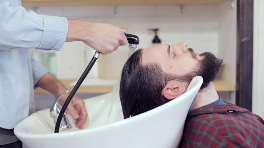 Man washing hair in salon barbershop hair wash stock for The barbershop a hair salon for men