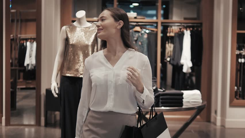 Woman coming out of the clothes store with bags. Girl go from entrance of luxury shop in mall. | Shutterstock HD Video #21744052