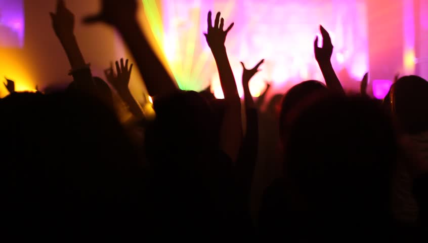 Crowd of people illuminated by colorful light during a concert