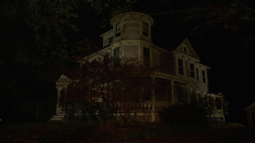 Night beige wood clapboard house , wrap around porch, back porch, bay windows, turret, dormers, autumn, fall trees, only porch lights on, (Oct 2012)