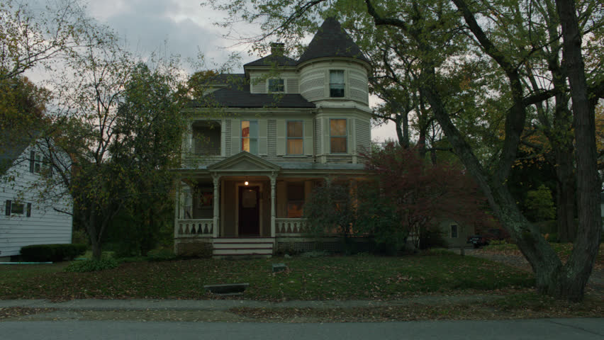 Day late day, dusk pans left front beige wood clapboard house , wrap around porch, bay windows, turret, dormers, red screened door, autumn, fall trees, breezy, lights on, (Oct 2012)