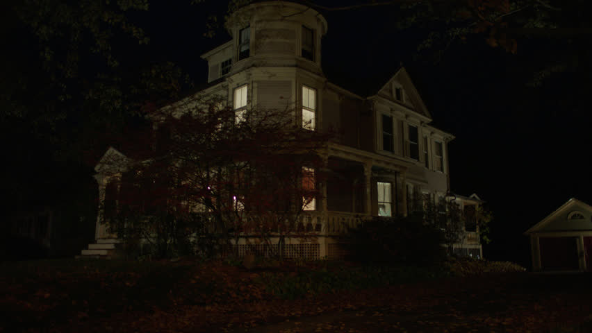 Night then tilts up beige wood clapboard house , wrap around porch, back porch, bay windows, turret, dormers, detached garage, autumn, fall trees, lights on, (Oct 2012)