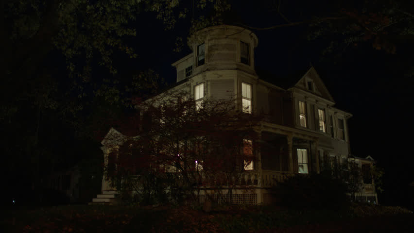 Night then tilts up left beige wood clapboard house , wrap around porch, back porch, bay windows, turret, dormers, detached garage, autumn, fall trees, lights on, (Oct 2012)
