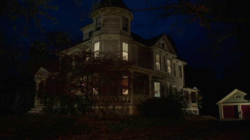 Night then tilts up corner side beige wood clapboard house , wrap around porch, back porch, bay windows, turret, dormers, detached garage, autumn, fall trees, lights on, cloudy, (Oct 2012)