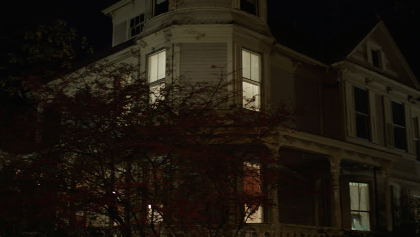 Night up then pans left along right beige wood clapboard house , wrap around porch, back porch, bay windows, turret, dormers, autumn, fall trees, lights on, (Oct 2012)