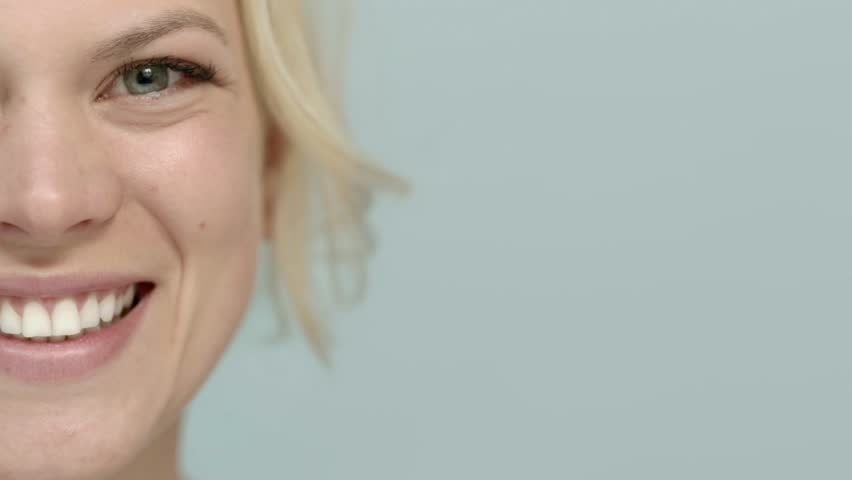 Beauty portrait, beautiful caucasian blonde woman smiling at camera. Cropped view, blue background, copy space - HD stock video clip