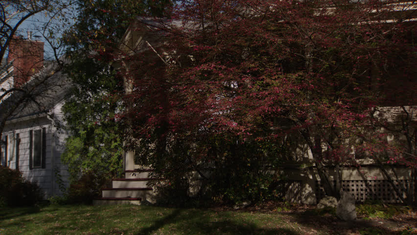 Day wrap around porch hidden behind trees beige wood clapboard house , autumn, fall trees, (Oct 2012)