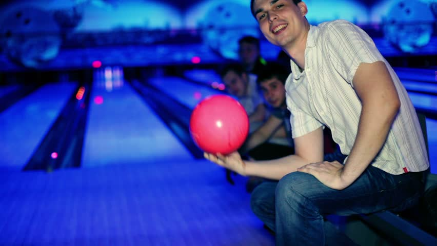 Young man holds pink bowling ball and then throws it, his friends support him