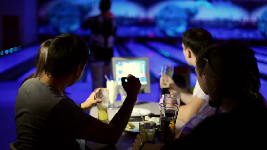 Young man makes strike in bowling game, his friends cheers hum and drink beer in dark club