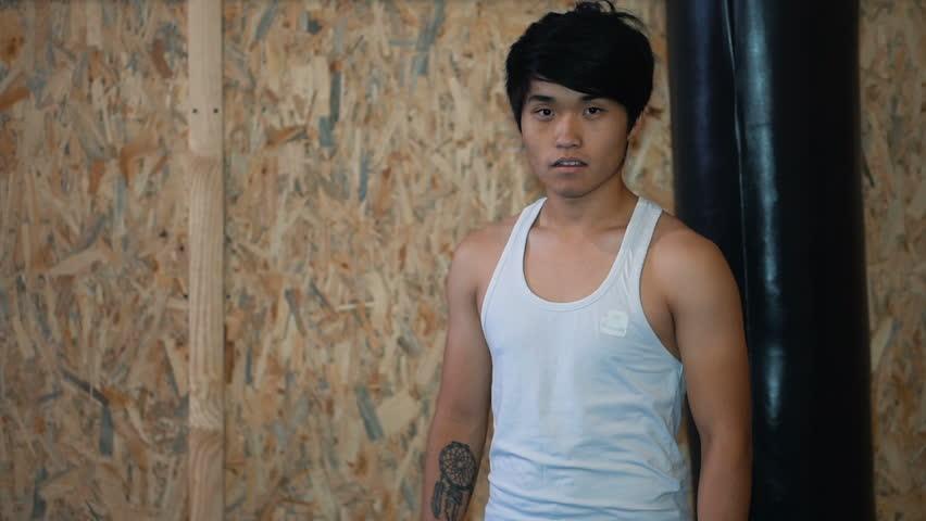 Young man beside punching bag | Shutterstock HD Video #21908041