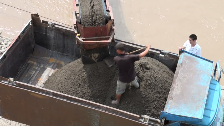 CHONGQING - 17 AUGUST: A man shovels sand into a truck on August 17, 2010 in Chongqing, China - HD stock footage clip