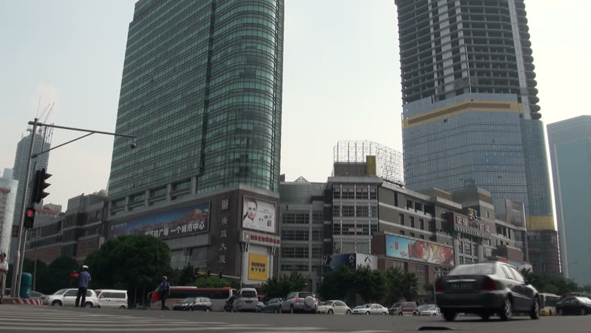 GUANGZHOU - 9 AUGUST: Traffic passes a large shopping mall August 9, 2010 in Guangzhou, China - HD stock footage clip