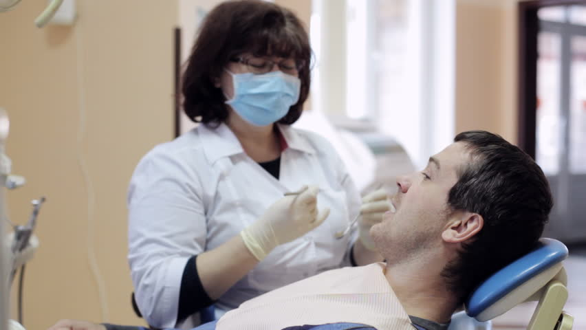 Middle years female dentist checks teeth of male patient by dental mirror | Shutterstock HD Video #21974038