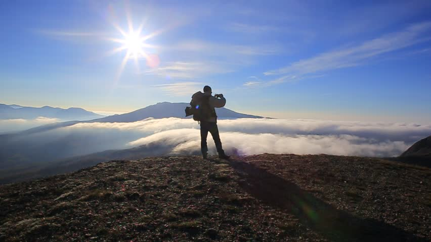 Traveller man with backpack stands at the top of the mountain with blue sky and sun above and clouds fast floating below and takes a picture of beautiful landscape with his smartphone. | Shutterstock HD Video #22050808