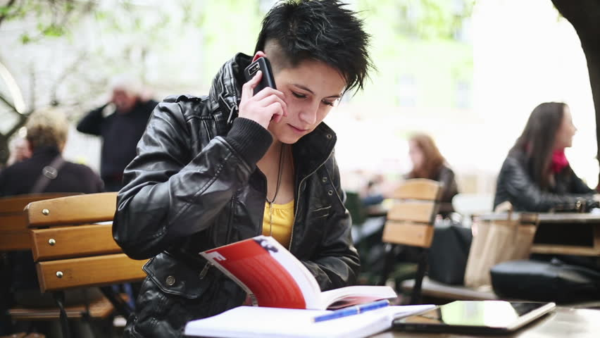 Young punk girl with cellphone and books outdoors