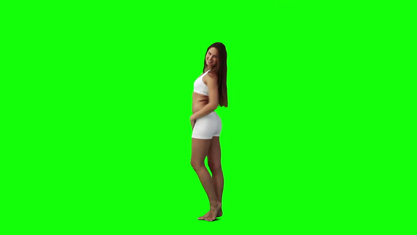 A woman is doing poses for the camera against a green background - HD stock video clip