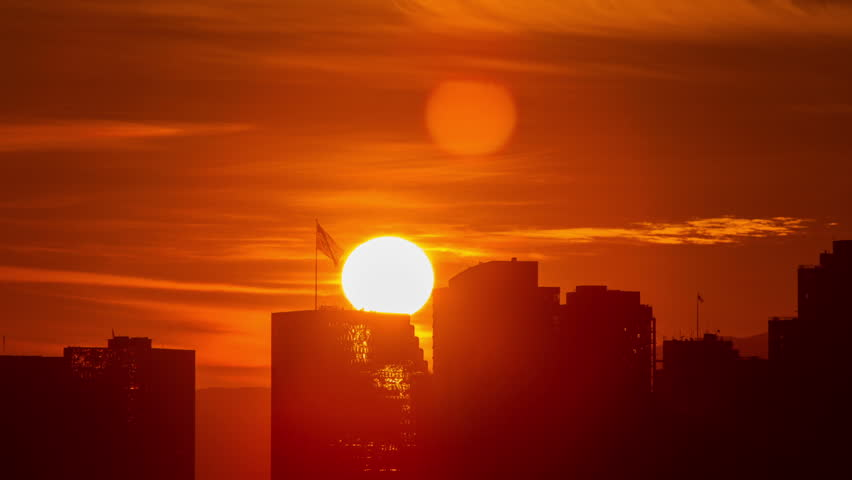 Time lapse of the sun rising from behind the buildings of downtown San Diego.   Shutterstock HD Video #22201495