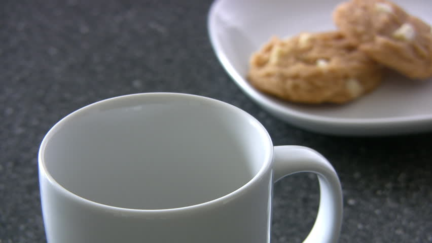 Pouring Hot Coffee Into A Mug At A Restaurant With Cookies In The Background