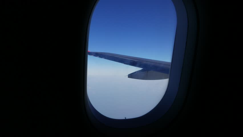 Plane wing visible through window, flight on cruise altitude. Aircraft and wing have small shakes because of a little turbulence at the height. #22366438