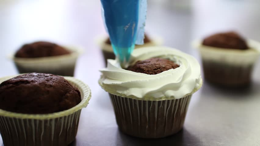 Decorating chocolate cupcake with cream. Using cooking bag, confectioner making cupcakes for party, Squeezing cream on delicious cupcakes #22393897