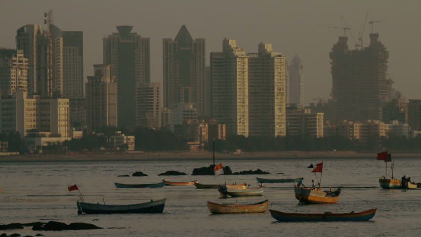 Mumbai city skyline in sunset, with boats on the water in the foreground.
