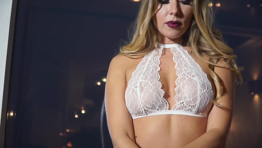 Beautiful girl in a white lace bra coyly corrects long hair | Shutterstock HD Video #22642945