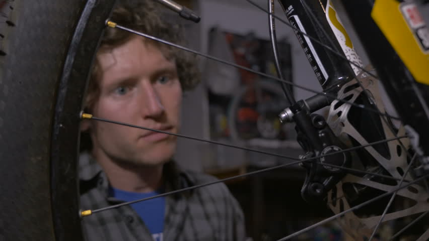 A young attractive bicycle mechanic working on a mountain bike with a long allen wrench - dolly shot | Shutterstock HD Video #22667722